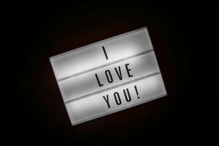 Lightbox with message I LOVE YOU isolated on black background. Inscription glows in dark. Concept of warmth feeling, declaration of sympathy, affection, tenderness, care, St. Valentines Day Foto de archivo