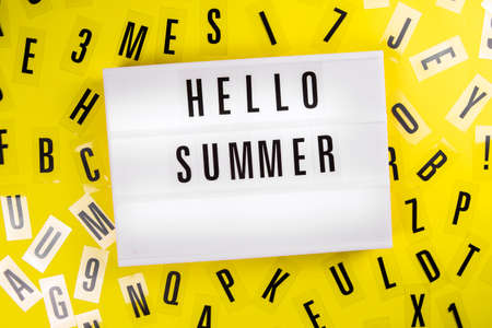 Lightbox with text HELLO SUMMER on yellow background with black letters randomly scattered. Concept of summertime, hot travel season, vacation, holiday, event ad, offer, sale, discount, promotion