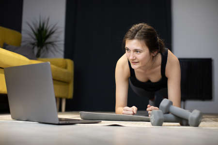 Smiling Girl stands in plank on floor looking at laptop counting seconds