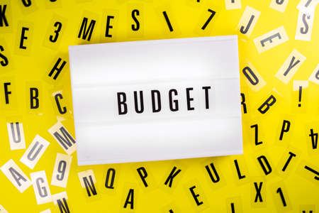 Lightbox with text word BUDGET on yellow background with black letters around. Concept of business, financial, money, expences, income, taxes, cheap price, annual project, statistics, corporate