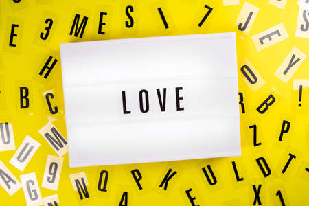 Lightbox with text message LOVE on yellow background with black letters randomly scattered. Concept of philanthropy, humanity, deep relationship, kindness, valentines day, wedding, anniversary Foto de archivo