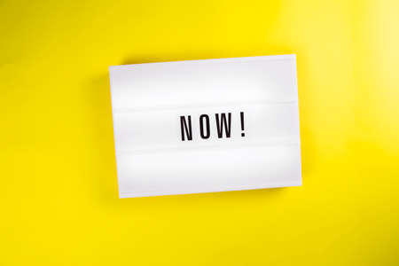 Lightbox with message NOW isolated on yellow background. Concept of motivation, hurry up sale announcement, start, beginning, buy now, register, join immediately, in stock, new trends, presently