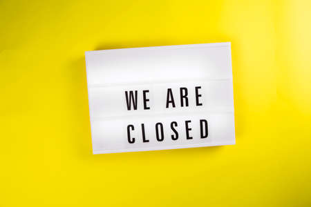 Lightbox with message WE ARE CLOSED isolated on yellow background. Concept of lockdown, business problems, holiday not working season, bankruptcy, liquidation, new normal, remote work, distance study