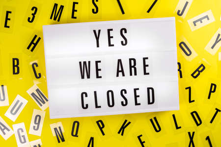 Lightbox with text YES. WE ARE CLOSED on yellow background with black letters randomly scattered. Concept of not working, pause business, not open office, school closure, distance study, education