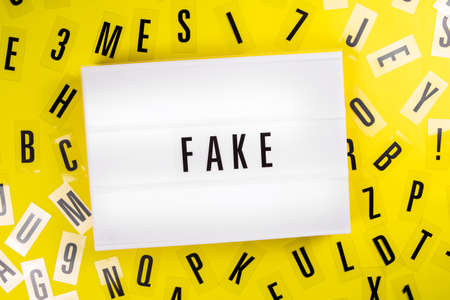 Lightbox with text message FAKE on yellow background with black letters randomly scattered. Concept of manipulation, false information, agitprop media, brainwashing, plugging, info hype, phishing