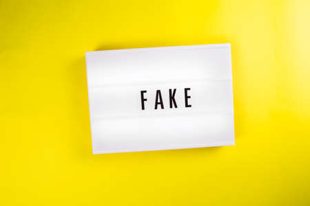 Lightbox with text message FAKE isolated on yellow background. Concept of fake not sincere emotions, relationship, job, fake material, fur, not real documents, fake information, person, fake Foto de archivo