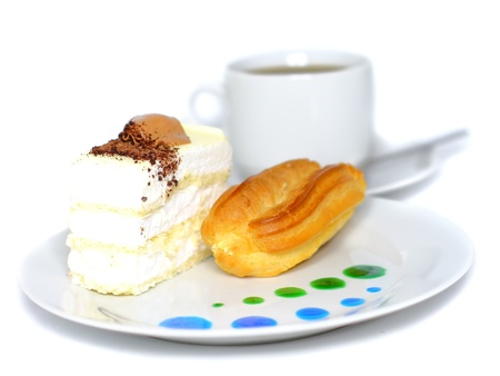 Sponge cakes and eclair cake on plate with fruit juice spots. Isolated photo