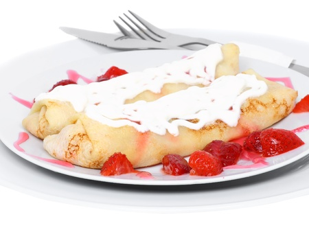 Pankcake with cream , with rolled fruit inside and strawberry around. Isolated photo
