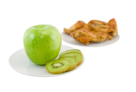 unwholesome: Opposition-healthy meal apples and kiwi, or unhealthy meal on background- roast chiken. Isolated Stock Photo