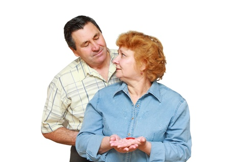 Old couple, wife hold  a small heart. Isolated over white photo