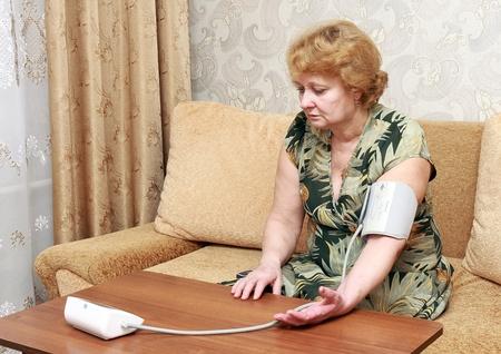 Old woman measures arterial pressure  in room. Stock Photo - 10276478