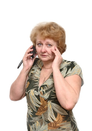 Senior lady speaks by a mobile phone . Isolated over white photo