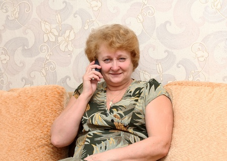 Senior lady speaks by a mobile phone . photo
