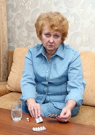 Senior lady woman with medication pills in room. photo