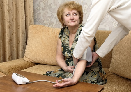 Old woman measures arterial pressure , with doctor helps. Stock Photo - 10276427