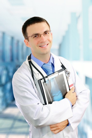 Friendly medical doctor stand with a x-ray image and medical pad in a Hospital. Stock Photo - 10275771