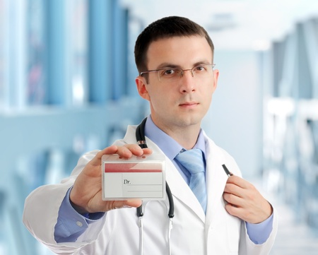 houseman: Friendly medical doctor with blank card (badge) in Hospital.