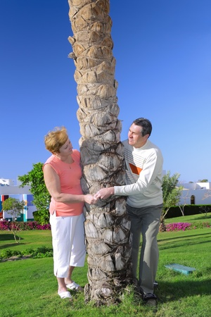 Mature couple near palm-tree  looked at each other with love. In tropical resort. Stock Photo - 10276417