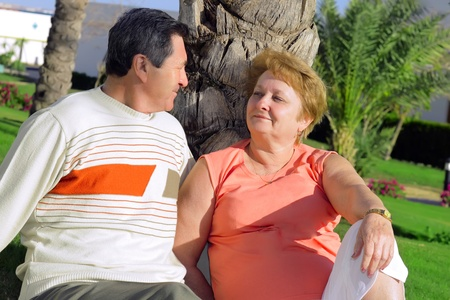 Mature couple near palm-tree  looked at each other with love. In tropical resort. photo