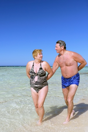 Mature couple walking on the beach in tropical resort. photo