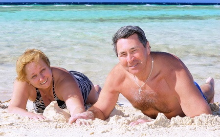 Mature couple on the beach in the tropical resort. Stock Photo - 10276424