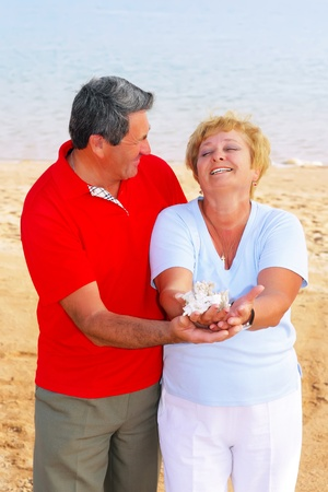 Elderly couple on the coast , holding seashells and corals in his arms. photo