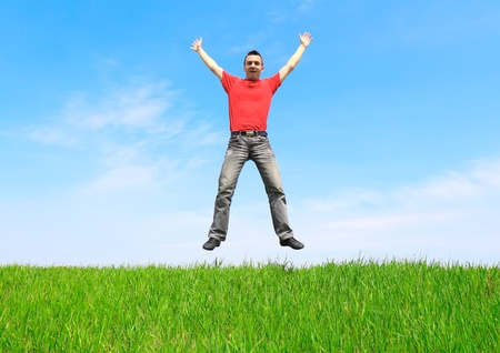 Young man jump on the meadow in summer day. photo