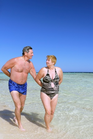 russian man: Mature couple walking on the beach in tropical resort.