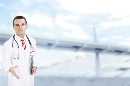 houseman: Doctor stand near the Hospital main Entrance. Outdoor Stock Photo