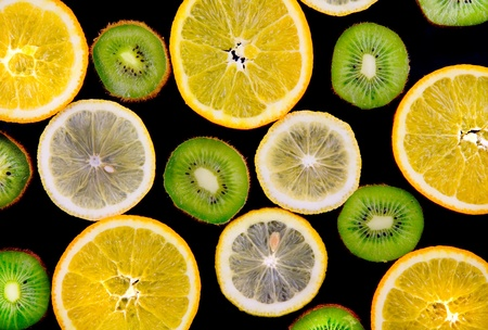 Background texture-fruit mix: lemon, orange, kiwi on black background. Stock Photo - 10276608