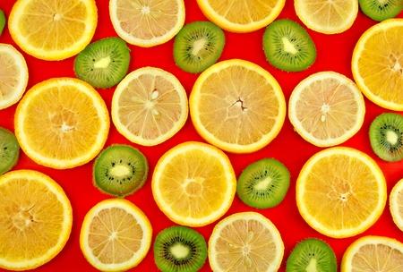 Background texture-fruit mix: lemon, orange, kiwi on red background. Stock Photo - 10276599