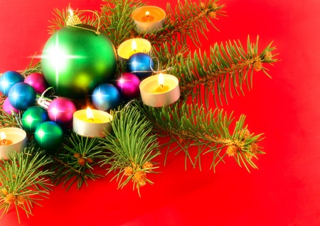 Christmas and New Year decoration-balls with fir branches and candels on red background . photo