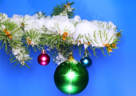 Christmas and New Year decoration- balls with real snow-covered fir branches .On blue background photo
