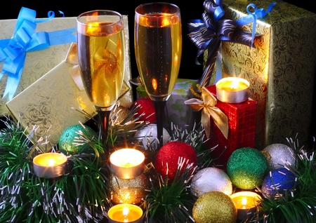 Christmas and New Year decoration- balls, tinsel, candel and glasses of champagne .On black background. photo