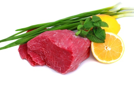 lean: Cut of  beef steak with lemon slice and onion. Isolated. Stock Photo