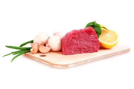 hardboard: Beef steak  on meat hardboard with mushroom  and lemon. Isolated. Stock Photo