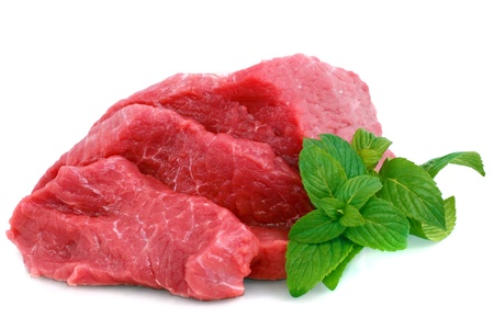 Cut of  beef steak with green leaf. Isolated. photo