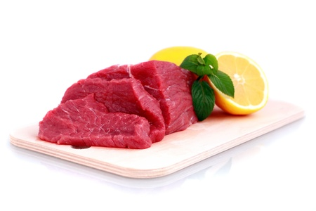 Beef steak  on meat hardboard with green leaf and lemon. Isolated. photo