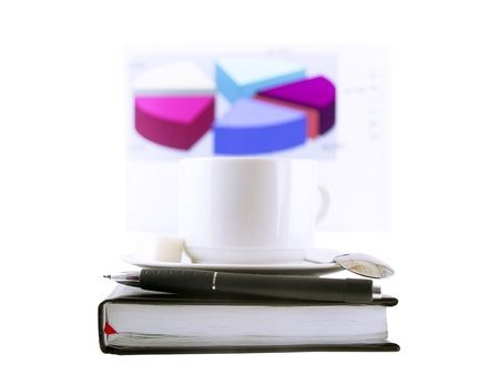 datebook: Coffee cup, standing on the personal organizer, on a back background-financial diagrams . Isolated Stock Photo