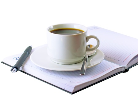 Coffee cup, standing on the opened daily organizer . Isolated photo
