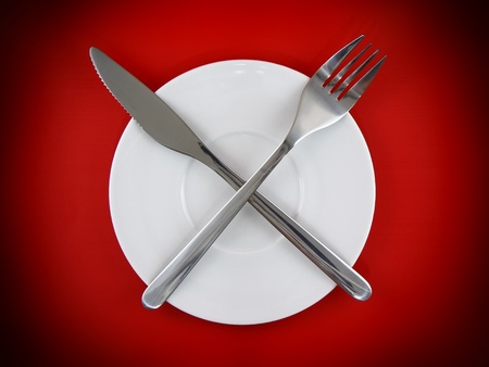 Table serving-knife,plate,fork on  red colour background. photo