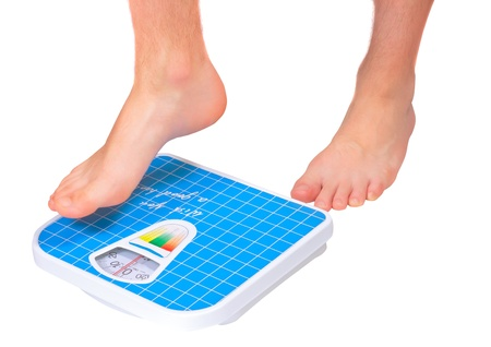 overeat: Mans legs , which weighed on floor scale. Isolated over white