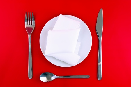 Table serving-knife,plate,fork and silk napkin  on  red colour background. photo