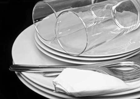fork glasses: Pile di piatti bianchi, bicchieri con forchette e cucchiai su tovagliolo di seta. Sfondo nero Archivio Fotografico