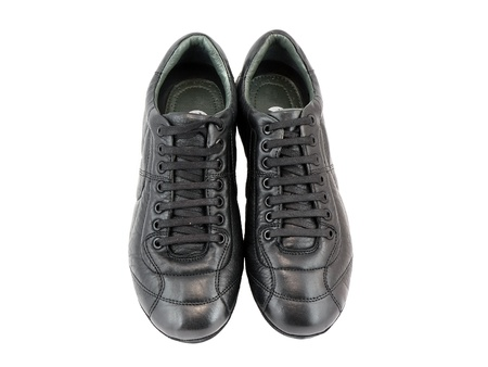 Leather black sneakers on white. Isolated over white. photo