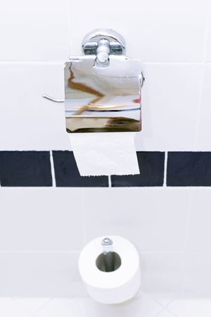 Roll of toilet paper holder in the  white toilet. photo
