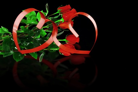 St. Valentine Day. Intertwining of two hearts, on black background with red roses.