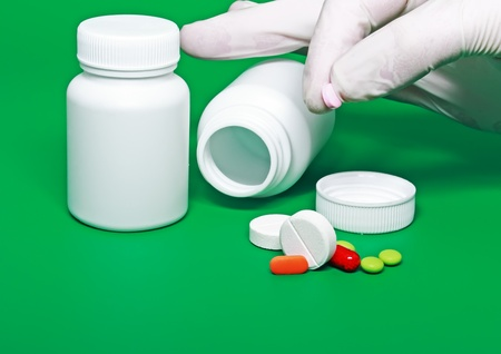 White medicine bottles,color pills on colour background. photo