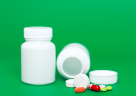 White medicine bottles,color pills on colour background. photo