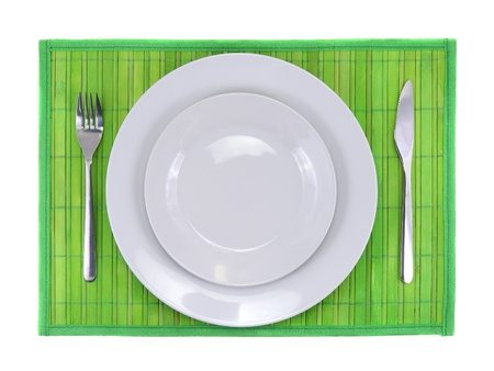 Table serving-knife,plate,fork on  green colour background. photo